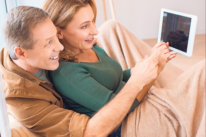Ein Pärchen sitzt auf der Couch und schaut gemeinsam auf ein Tablet. Thema: Feedbacksystem