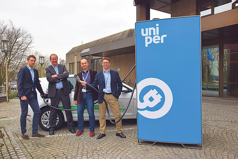 Mitarbeiter von Uniper stehen vor einer Schnellladesäule