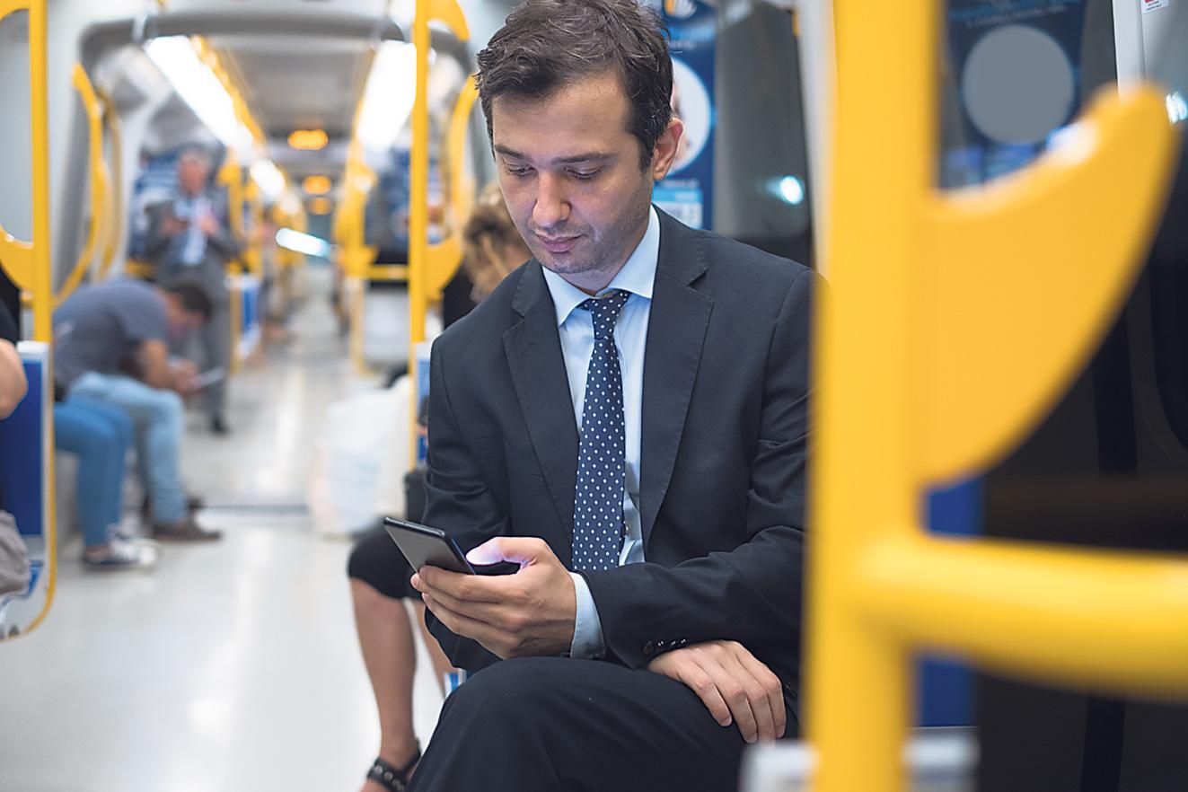 Geschäftsmann sitzt in der Bahn und nutzt sein Smartphone. Thema: Mobilitätsplattformen
