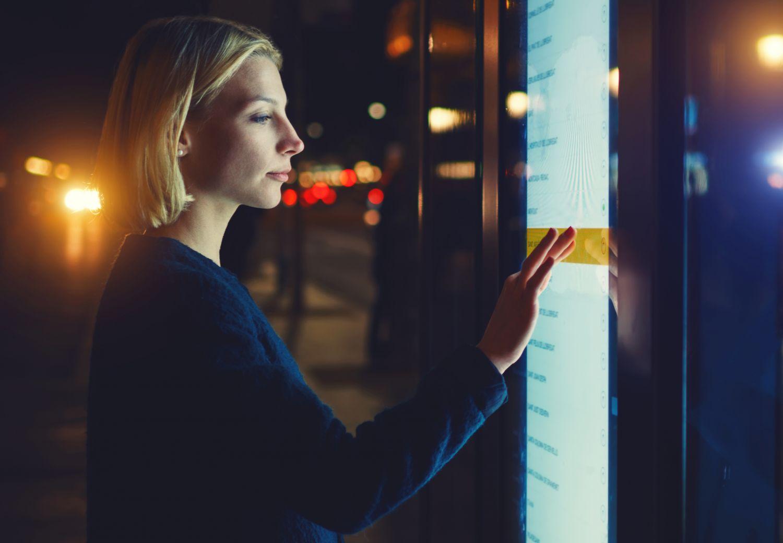 Eine Frau an einem öffentlichen Touch Screen. Die Smart City erlaubt, sich einfach digital durch den Großstadtdschungel zu lotsen.