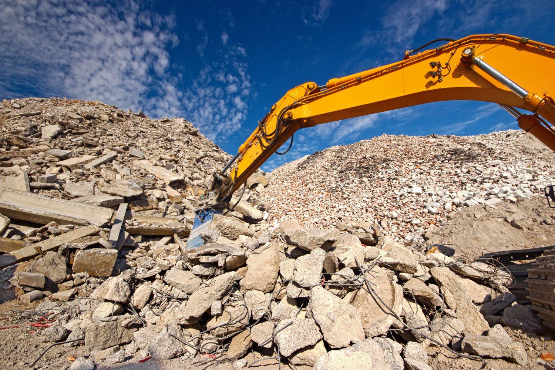 Abbruchbagger in Bauschutt; Thema: Urban Mining