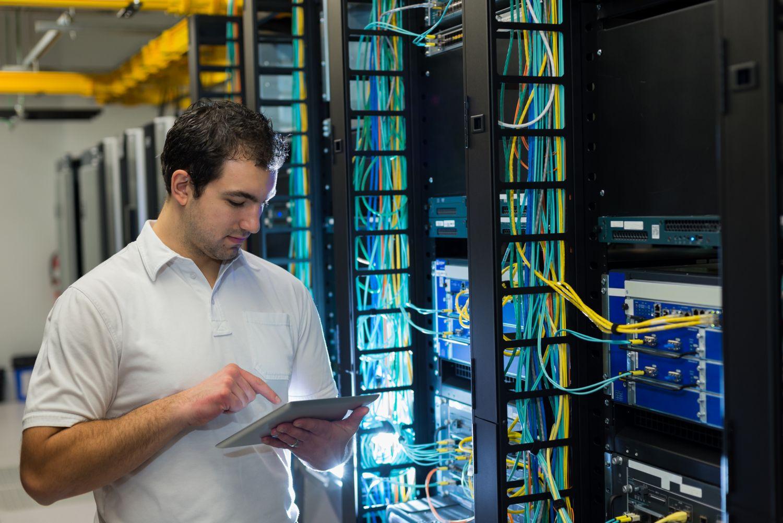 Ein Mann steht in einem Serverraum. Thema: Strukturierte Verkabelung