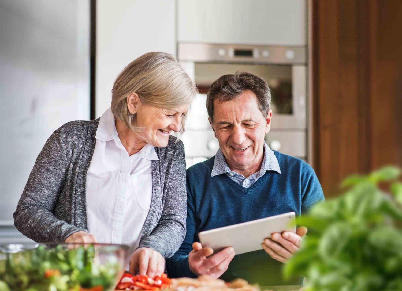 Älteres Pärchen schaut sich auf einem Tablet Informationen an.