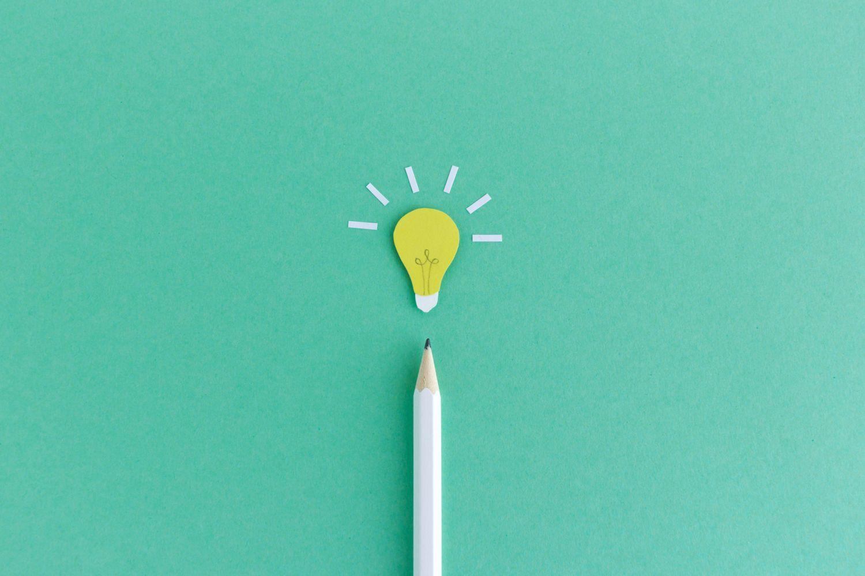 Ein Bleistift und eine gezeichnete Glühlampe: Symbolbild für Wissen