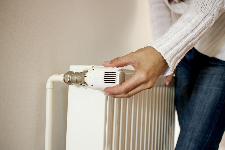 Eine Person dreht am Thermostat: die staatliche Förderung von Wärmepumpen motiviert zur Modernisierung.