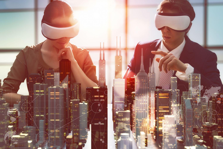 Ein Mann und eine Frau mit VR-Brillen betrachten das Modell einer Stadt. Thema: Vernetzung
