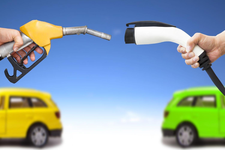 Eine Zapfventile für fossilen Kraftstoff steht einem E-Zapfventil gegenüber. Beide Fahrzeugvarianten konkurrieren miteinander.