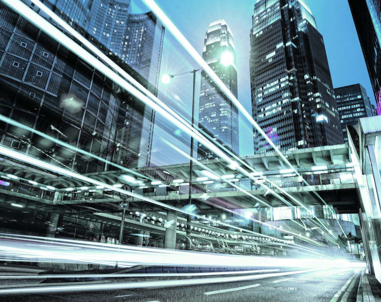 Lichter von Autos auf Straßen, die zwischen Hochhäusern entlang führen. Thema: Nachhaltiger Städtebau