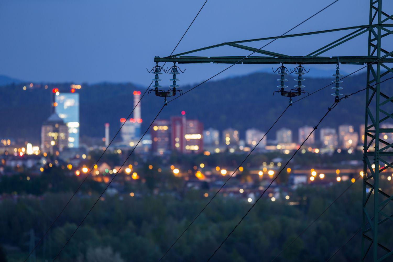 Nächtliche Skyline einer Stadt von einer Stromtrasse aus gesehen. Thema: Smarte Energienetze. Foto: Getty Images Plus / Urban78