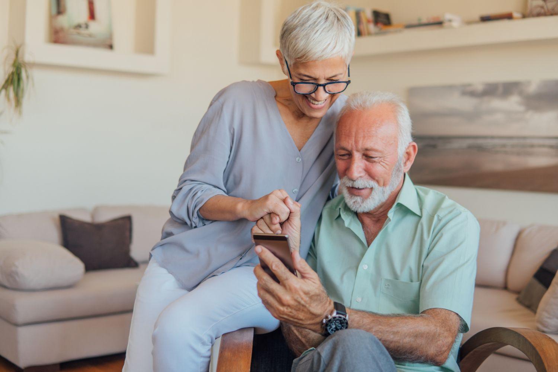 Ein älteres Ehepaar schaut zusammen auf ein Smartphone. Thema: Seniorengerechtes Wohnen