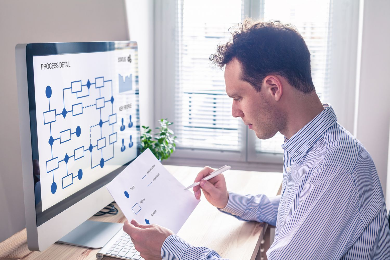 Ein Mann studiert einen Plan. Thema: Gebäudeautomatisierung