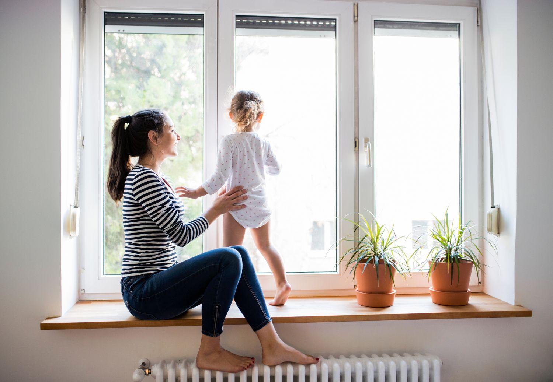 Eine Mutter spielt neben einer Heizung mit ihrem Kind. Thema: innovative Energie